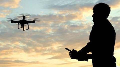 Com um céu nublado, de tons azuis-escuros e roxos como fundo, as imagens a contra-luz de um drone a funcionar, em cima à esquerda, e de um homem a manipulá-lo, em baixo, à direita.