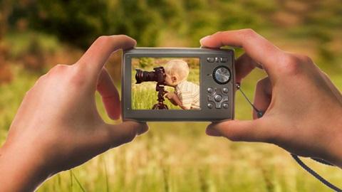 Imagem desfocada de uma paisagem como fundo. Em primeiro plano, duas mãos agarram uma máquina fotográfica, em cujo visor é possível ver a imagem de uma criança loira a espreitar pela objetiva de uma máquina fotográfica.