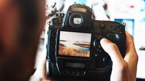 Homem a testar máquina fotográfica
