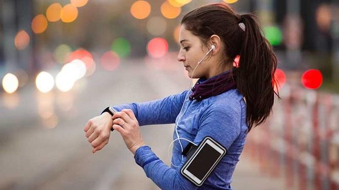 Mulher com roupa de desporto a verificar app de exercício no smartwatch.