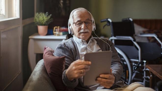 Senhor sénior sentado num sofá, com um tablet nas mãos