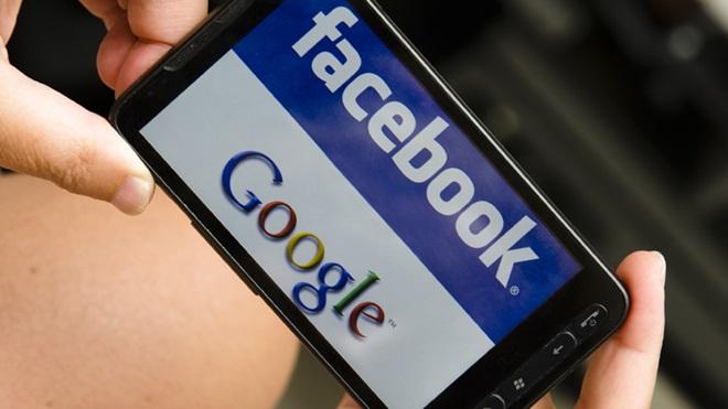 Mãos a segurar um telemóvel com palavras Facebook e Google