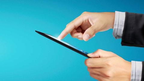 Sobre um fundo azul-turquesa compacto, vemos, ao centro, um tablet, que é agarrado e manipulado, do lado direito, por duas mãos masculinas (cujos punhos exibem os punhos de uma camisa cinzenta-clara e de um blazer preto).
