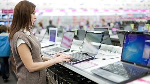 Numa loja de eletrónica, na secção dos computadores portáteis, uma jovem cliente, vestindo uma t-shirt branca e um vestido quente de malha sem alças, de cor castanha-clara, experimenta um dos portáteis em exposição.