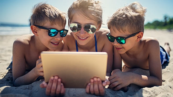 Crianças a usar o tablet na praia