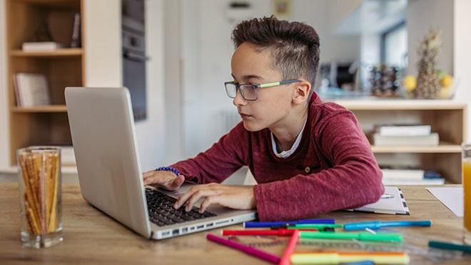 Criança a estudar em casa num computador portátil