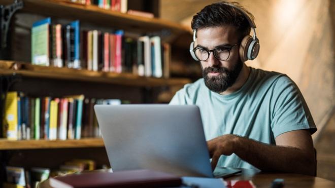 homem a trabalhar em casa à secretária no computador
