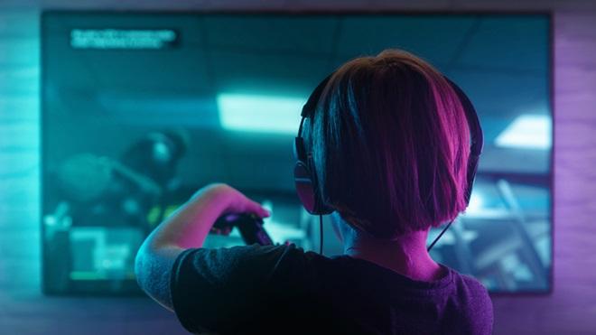 Criança em frente a um monitor, a jogar numa consola e com auscultadores na cabeça