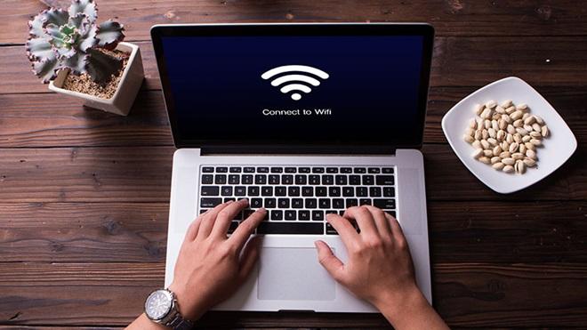 mãos a escrever em computador portátil numa secretária