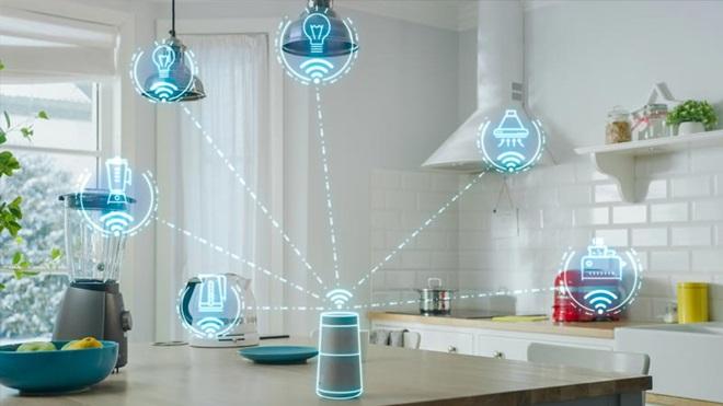 Cozinha banhada de luz e com paredes brancas, com vários aparelhos conectados à net via wi-fi, alguns em cima de uma mesa de madeira escura