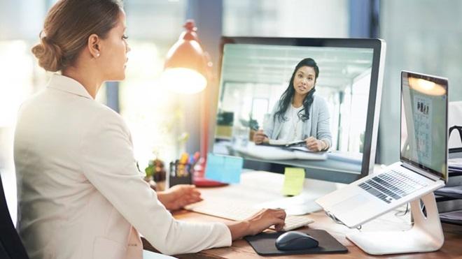 Mulher jovem à secretária, a trabalhar no computador portátil e com um monitor externo, por onde assiste a uma videoconferência