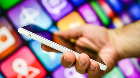 Pessoa a segurar o telemóvel enquanto trabalha com apps móveis