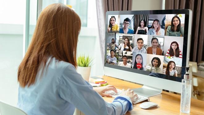 Mulher a trabalhar num computador e a assistir a uma videoconferência, com o frasco de álcool-gel em cima da mesa