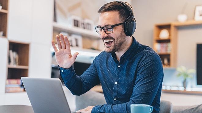 Homem com auscultadores a participar numa videoconferência através de um computador portátil