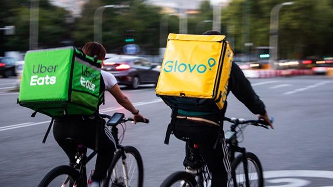 Duas pessoas de bicicleta com mochilas da ubereats e da glovo