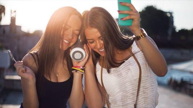 Duas jovens na rua, a ouvirem música através de uma coluna de som bluetooth emparelhada com o telemóvel