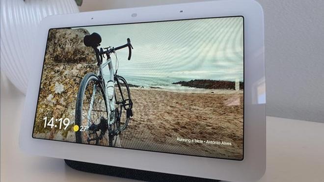 Google Nest Hub em cima de uma mesa, exibindo uma fotografia de uma bicicleta numa paisagem de praia
