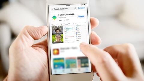Plano aproximado de um telemóvel de cor branca, ao centro da imagem, manipulado por duas mãos. No ecrã do telemóvel, o resumo daquilo que parece ser uma app de controlo parental, numa loja de apps.