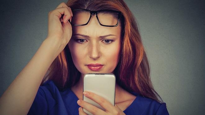 Pessoa a olhar sem óculos para ecrã do smartphone