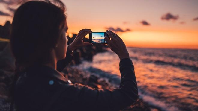 Mulher a fotografar com um telemóvel, junto ao mar, ao pôr-do-sol