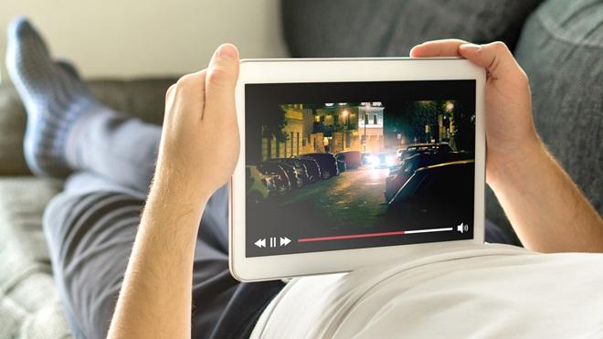Rapaz a ver um filme no tablet, enquanto está deitado na cama