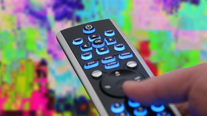 mão a pressionar comando de televisão para sintonizar canais de TDT