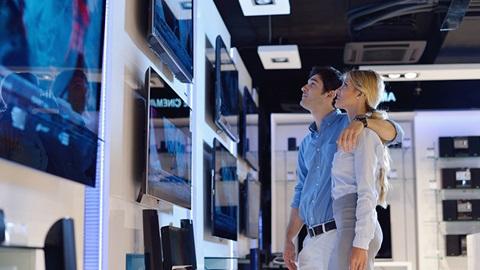 Numa loja de eletrónica, na secção dos televisores, um jovem casal observa alguns dos televisores em exposição. O homem do casal é moreno, enverga uma camisa azul e calças claras, com um cinto castanho, e abraça a mulher. A mulher é loira e veste uma camisa azul-clara e calças cinzentas.