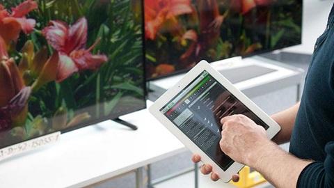 homem com tablet na mão a escolher televisor na loja