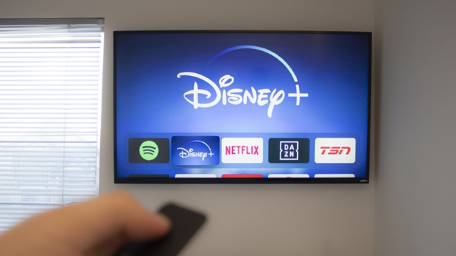 Mão a segurar num telecomando e a operar um televisor inteligente, montado na parede junto a uma janela, com diversas aplicações no ecrã, destacando-se a da Disney+