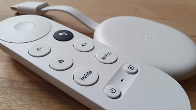 Chromecast com Google TV, sobre uma mesa de madeira, acompanhado pelo telecomando fornecido de origem