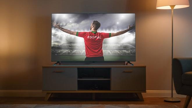 Televisão sobre uma mesa, numa sala com iluminação fornecida por um candeeiro de pé. No ecrã, pode ver-se um apoiante da seleção portuguesa de futebol, de costas e de braços abertos, virado para uma arena