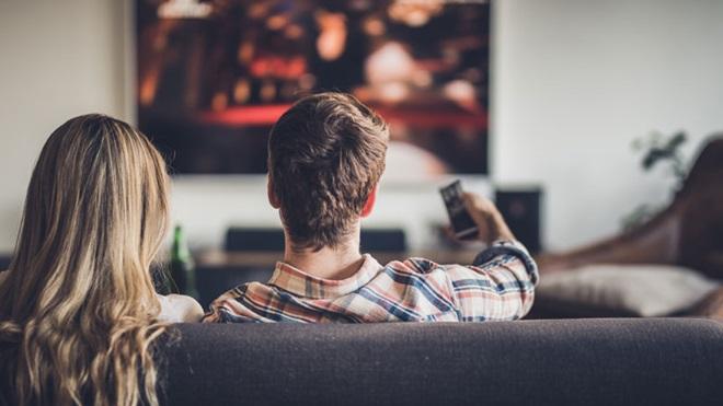casal sentado no sofá de costas a ver televisão