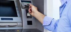 Pessoa a introduzir cartão de débito numa caixa multibanco