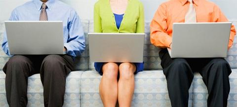 Três pessoas a utilizar computadores numa rede doméstica.