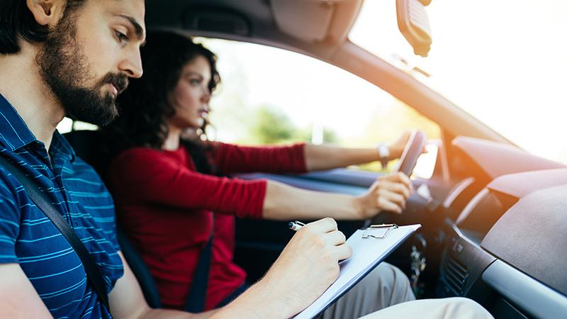 mulher a conduzir com homem a examinar a condução ao lado