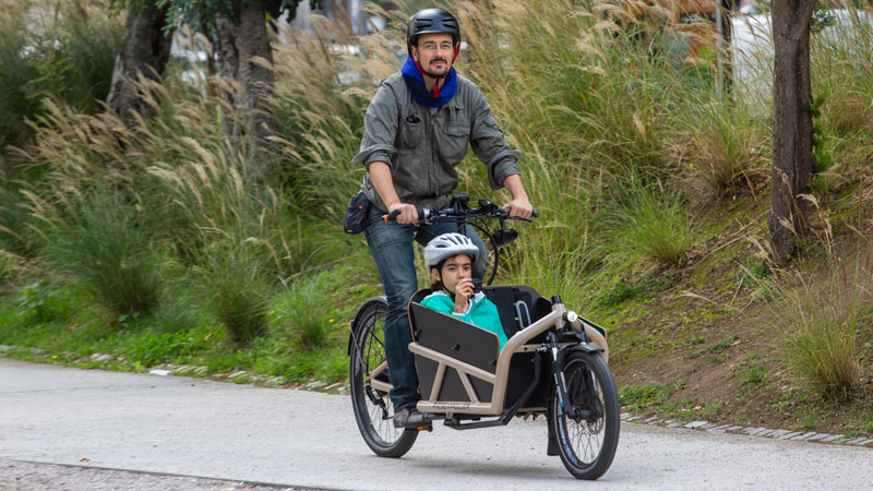 Pai e filha viajam em Lisboa de bicicleta elétrica.
