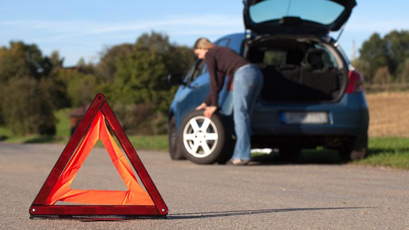 Triângulo de perigo na estrada com mulher ao fundo a trocar pneu furado