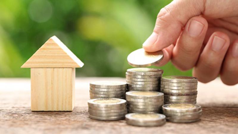 mão acrescenta moeda a um dos 7 conjuntos de moedas na imagem ao lado de uma casa de madeira que representa os rendimentos prediais