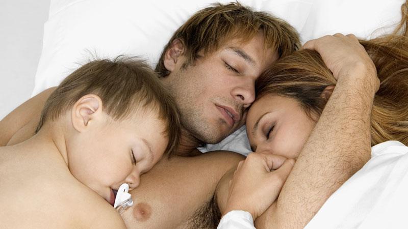 Casal com filho a dormir numa cama