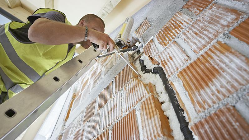 construtor a reforçar paredes de uma casa com materiais de isolamento térmico