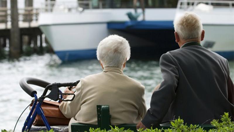 casal de idosos reformados a olhar o rio