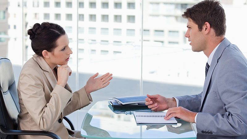 Mulher e homem a conversar sobre a rescisão do contrato de trabalho sentados no escritório