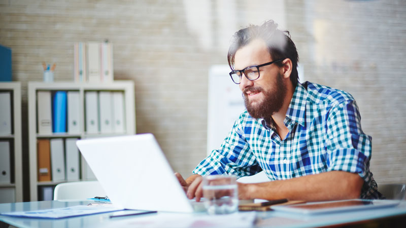homem a utilizar computador para validar as faturas pendentes no portal e-fatura