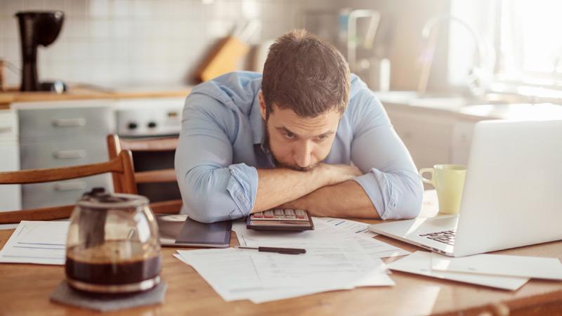 homem em secretária desesperado por preencher o IRS