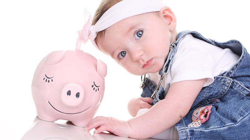 Bebé a olhar para um mealheiro em formato de porco