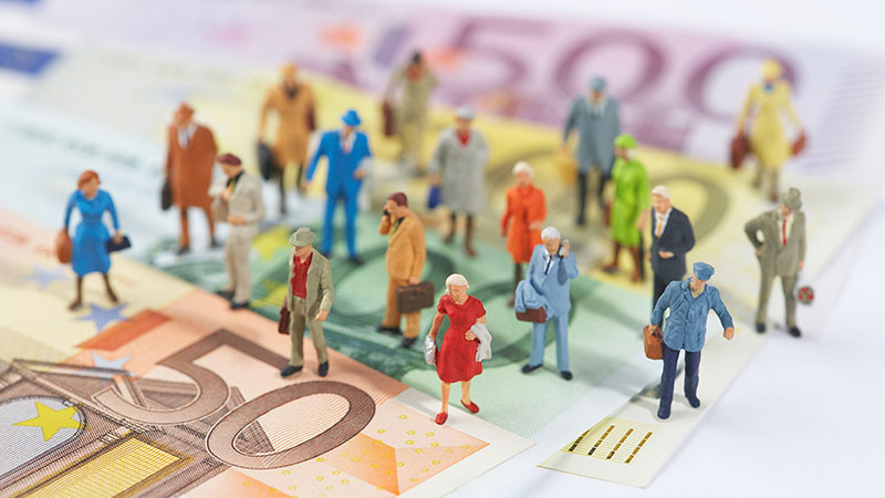 Bonecos que representam pessoas em cima de notas de euros