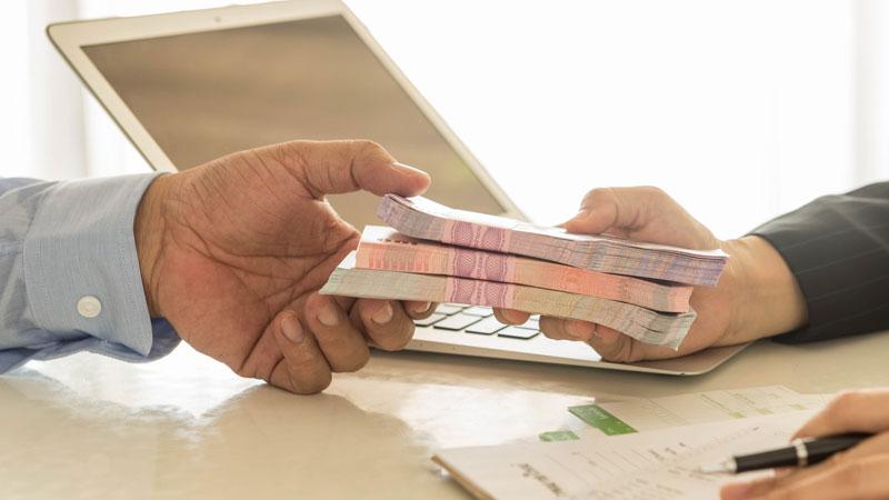 mão a entregar notas a outra mão para investimento