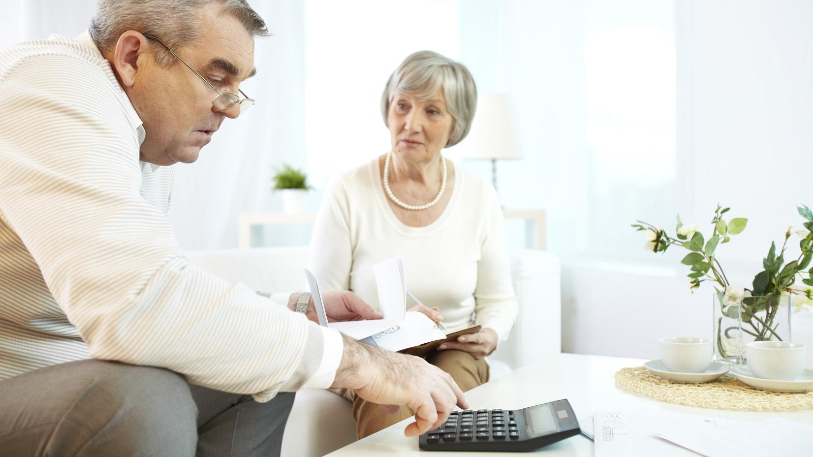 Casal idoso faz contas numa calculadora