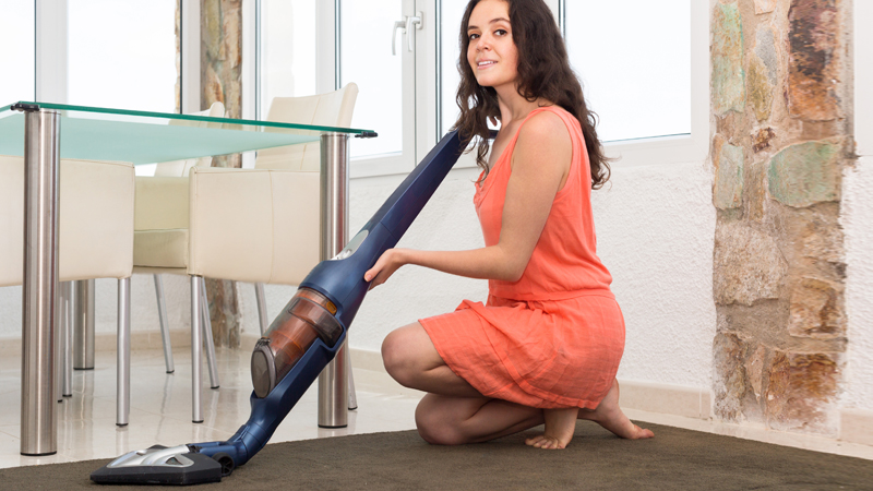 Mulher com aspirador vertical
