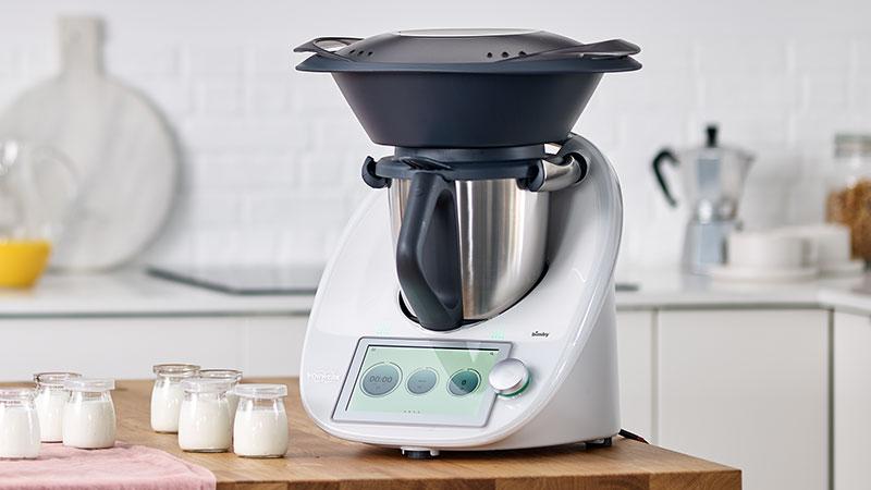 Bimby tm6 em cima da bancada da cozinha ao lado de copos de iogurte preparados no robô de cozinha